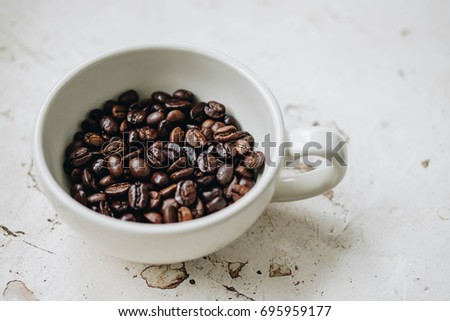Coffee beans close up in a coffee cup on vintage table in coffee shop