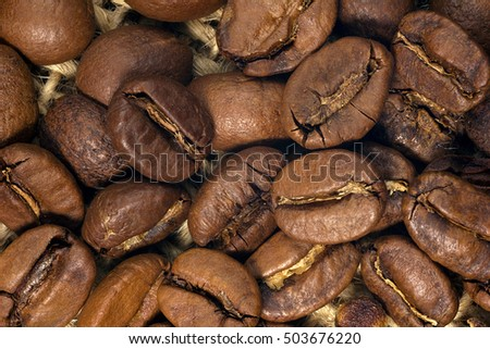 Coffee beans closeup on natural texture.