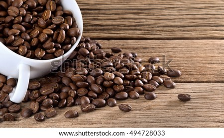 coffee beans. coffee beans background. coffee beans with white cup on wooden table.