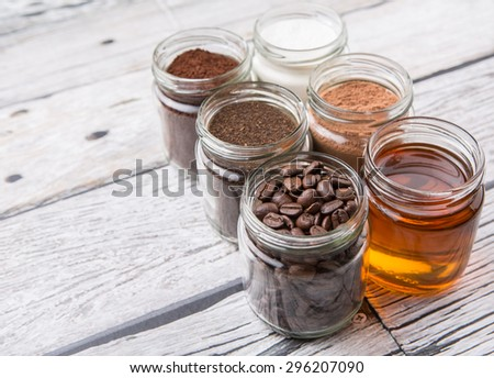 Coffee beans, coffee powder, creamer, cocoa powder, honey and processed tea leaves in a mason jar over weathered wooden background - stock photo