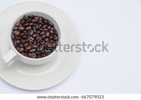 Coffee beans , coffee seeds  in a white coffee cup on white background