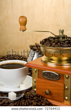 coffee beans, cup and grinder on wood texture