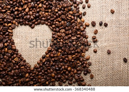 Coffee beans formed shape of heart on sackcloth background - stock photo
