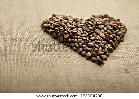 Coffee beans, grain heart on background of sacking, bagging. Valentine's Day or Wedding, love, black, frame. Heart shaped Coffee Beans