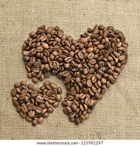 Coffee beans, grain two hearts on background of sacking, bagging. Valentine's Day or Wedding, love, black, frame. Heart shaped Coffee Beans. Big and small heart.