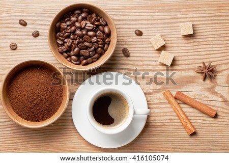 Coffee beans, ground coffee and cup of brewed coffee on rustic wooden table decorated cinnamon sticks, star anise, cane sugar and coffee beans, view from above - stock photo