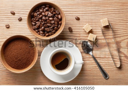 Coffee beans, ground coffee and cup of brewed coffee on rustic wooden table with spoon, sugar tongs, cane sugar cubes and coffee beans, view from above - stock photo