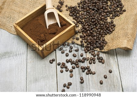 coffee beans, ground coffee with wooden spoon on rusty wood background
