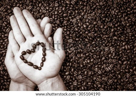 coffee beans heart symbol on top of the hand. Coffee beans texture underneath. - stock photo