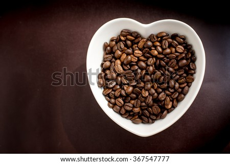 coffee beans in a bowl in the form of heart on a leather background with natural light.