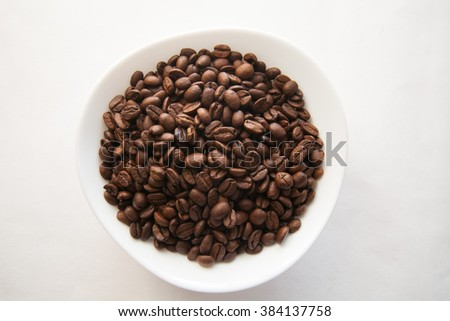 Coffee beans in a bowl on a white background