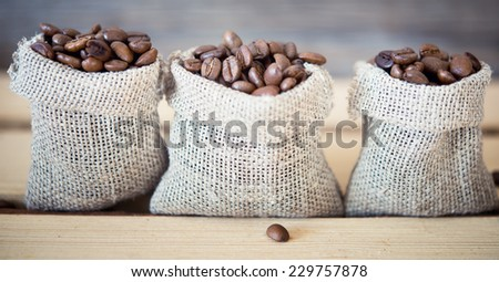 coffee beans in a burlap sack on wooden background - stock photo