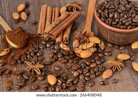 Coffee beans in a ceramic bowl and spices on wooden background - stock photo
