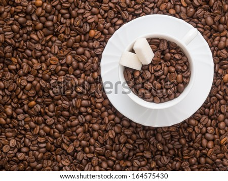 Coffee beans in a cup with pieces of sugar. background not in focus - stock photo