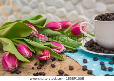 Coffee beans in a cup with pink tulips on wooden table - stock photo