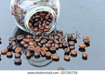 Coffee beans in a glass jar and some coffee beans on a shiny black table. - stock photo