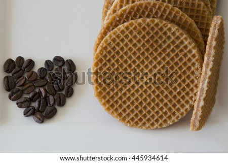 Coffee beans in a heart shape besides soft toasted dutch waffles filled with caramel  - stock photo