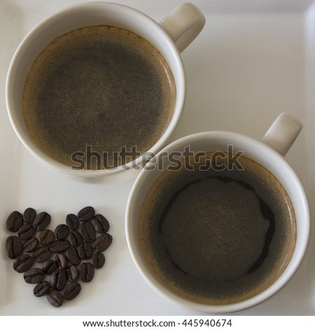Coffee beans in a heart shape besides two cups of coffee - stock photo