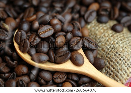 Coffee beans in a sack and a wooden spoon - stock photo