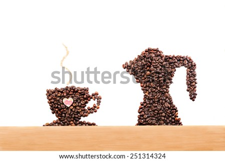 Coffee beans in a shape of coffee cup and coffee beans in a shape of coffee pot, green leaf on a white background and wood on bottom. Smell of coffee made from sugar - stock photo