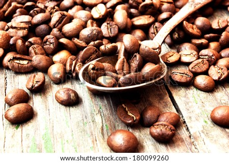 coffee beans in a spoon on wooden background