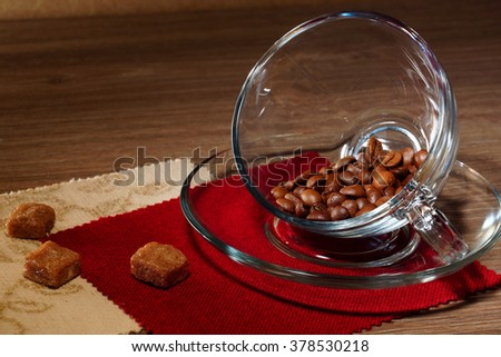 Coffee beans in a transparent cup and pieces brown sugar on the wooden table.