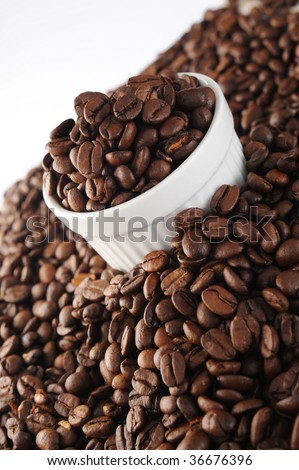 Coffee beans in a white ranikin and surrounding it, with dark gray background