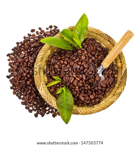 coffee beans in a wicker basket decorated with green leaves and spoon isolated on white background - stock photo