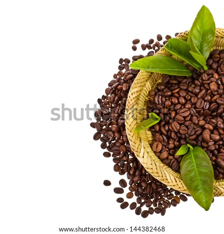 coffee beans in a wicker basket decorated with green leaves isolated on white background - stock photo