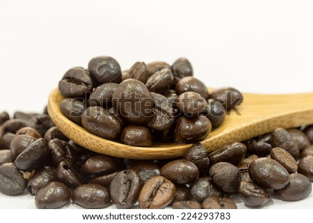 Coffee beans in a wooden spoon on white background