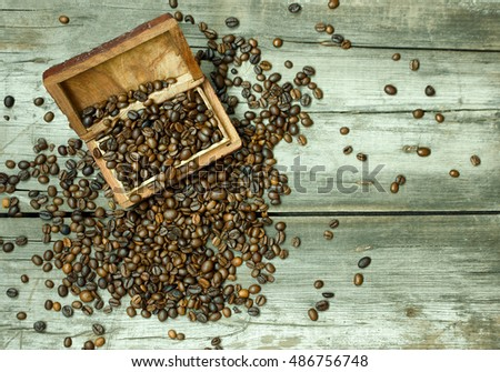 Coffee beans in a wooden vintage box on wooden background