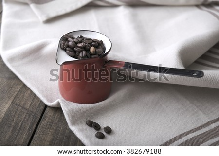 Coffee beans in an enamel mug on the wooden background - stock photo
