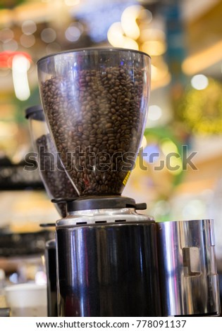 Coffee beans in blender blurred background.