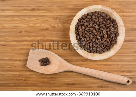 Coffee beans in bowl on wooden background - stock photo