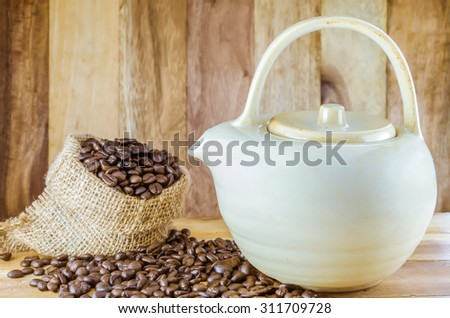 Coffee beans in burlap bag on wood background - stock photo