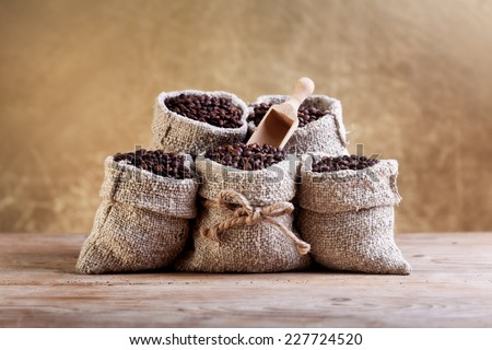 Coffee beans in burlap bags on old wooden table - stock photo