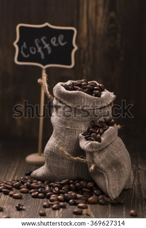 Coffee beans in burlap bags over wooden background. Vintage style. Toned image. Selective focus - stock photo