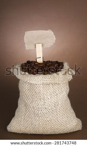 Coffee beans in burlap sack with a vintage price tag - stock photo