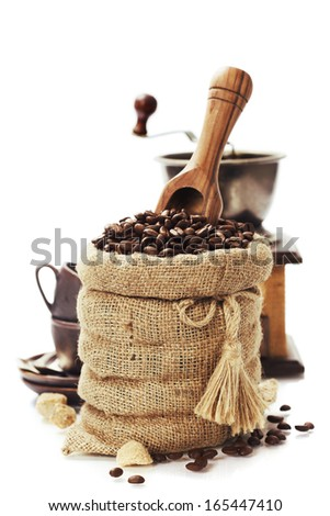 Coffee beans in burlap sack with wooden scoop  over white - stock photo