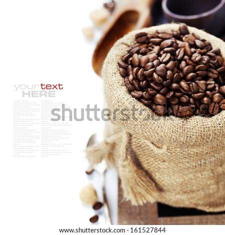 Coffee beans in burlap sack with wooden scoop  over white (with sample text) - stock photo