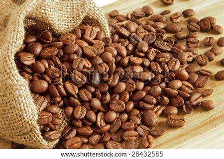 Coffee beans in canvas sack on wooden background - stock photo
