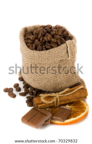 Coffee beans in canvas sack with cinnamon, chocolate and dried orange slice