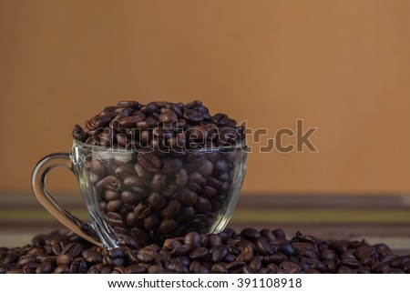 Coffee beans in clear cup close up - stock photo