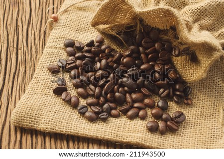 Coffee beans in coffee bag on wooden background