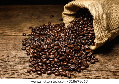 Coffee beans in coffee burlap bag on wooden surface.