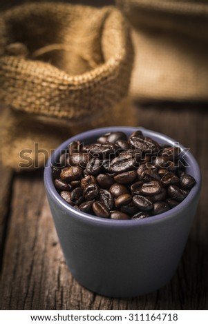 Coffee beans in coffee cup on wood table - stock photo