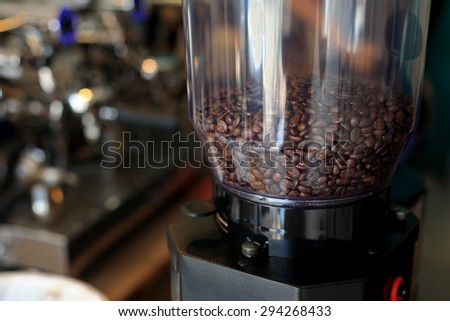 Coffee beans in coffee grinder near coffee maker machine