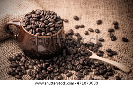 coffee beans in cup on sackcloth, vintage and dark tone
