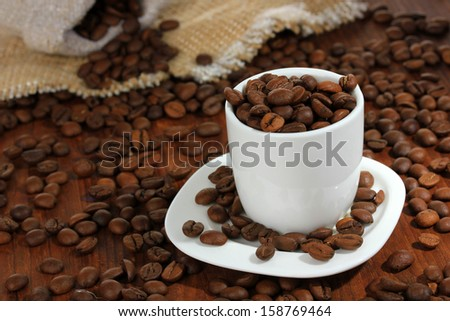Coffee beans in cup on wooden background