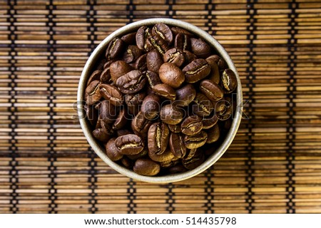 Coffee beans in cup with leaf symbol